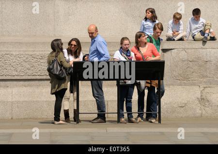 Londra, Inghilterra, Regno Unito. Famiglia guardando information board da Nelson della colonna Foto Stock