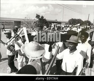 """Mar 26, 1969 - Il Sig. Lee ''sepolto """" Da Anguillans: Hynn cantando Anguilla trasportano un black-drappeggiato bara durante il funerale di simulazione per il Sig. Tony Lee, la Gran Bretagna è controverso Commissario nelle isole. Circa 500 abitanti seguita ''Pall-portatori'' por due miglia al Sig. Lee ufficio vuoto. La bara è stato utilizzato per ultimo quando gli isolani volevano estrarre un amministratore dall'odio San Kutts Governo due anni fa. Egli ha lasciato il giorno successivo."""