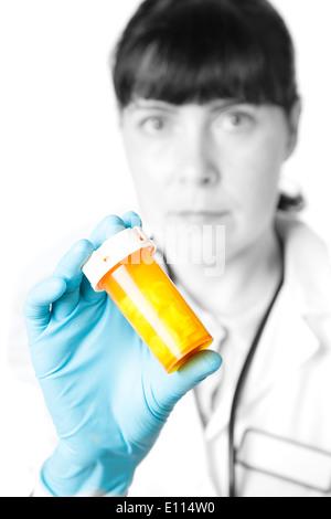 Il medico o il farmacista in possesso di una bottiglia di pillole Foto Stock