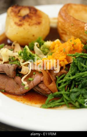 Arrosto di manzo cena con patate arrosto, Yorkshire pudding e purea di verdure svedese e samphire Foto Stock
