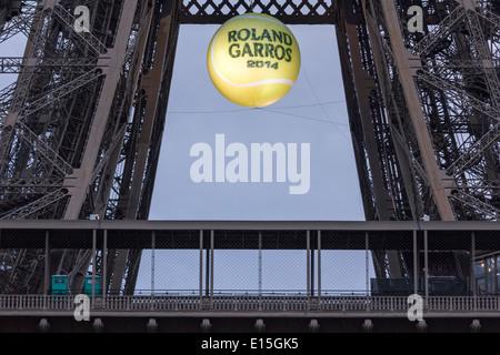 Torre Eiffel al tramonto con un gigante, illuminato palla da tennis appesa sopra la prima piattaforma per promuovere i 2014 francesi aperti.