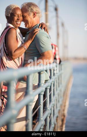 Coppia senior abbracciando sul molo Foto Stock