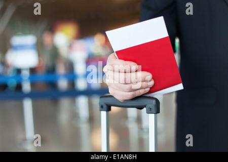 Chiusura del passaporto e biglietto in mano in aeroporto Foto Stock