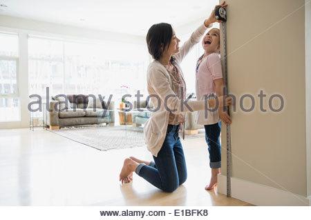 Madre figlie di misurazione altezza in salotto Foto Stock