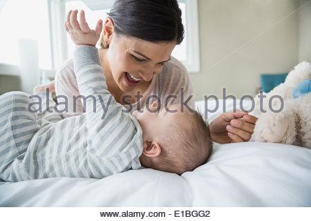 La madre e il bambino ridere sul letto Foto Stock