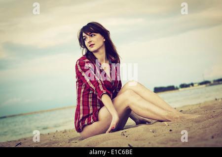 Giovane donna in un rosso controllato shirt rilassante sulla spiaggia al tramonto
