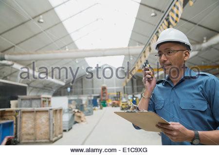 Lavoratore utilizzando un walkie-talkie in impianto di produzione Foto Stock