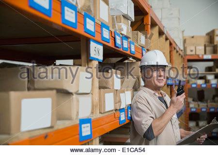 Lavoratore con un walkie-talkie in magazzino Foto Stock