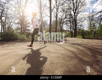 Sano giovane donna fare jogging nel parco. Fitness modello femminile in esecuzione nella foresta. Caucasica modello fitness esercizio all'esterno.