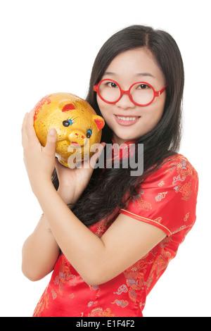 Bella donna cinese che indossa un abito tradizionale noto come un Chipao tenendo un salvadanaio Foto Stock