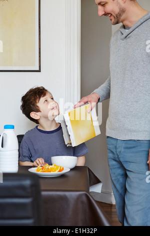Padre versando cereale in figlio la vaschetta