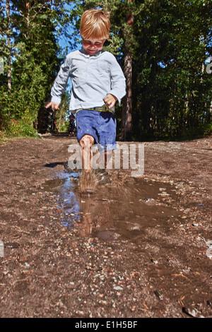 Ragazzo giovane schizzi nella pozza di fango Foto Stock