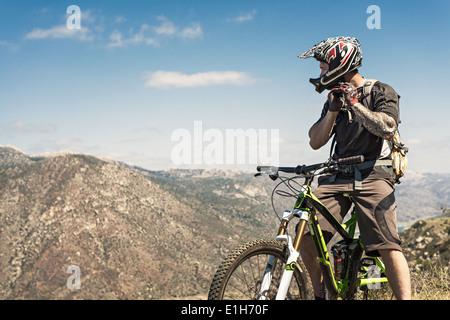 Downhill mountain biker mettendo sul casco Foto Stock