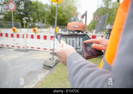 Close up foremans mani con tavoletta digitale su strada sito in costruzione