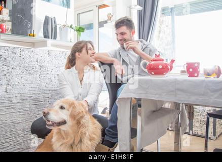 Coppia giovane avente la colazione, con il cane Foto Stock