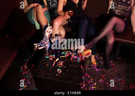 Ritagliato colpo di femmina mini fiancheggiò amici in discoteca Foto Stock