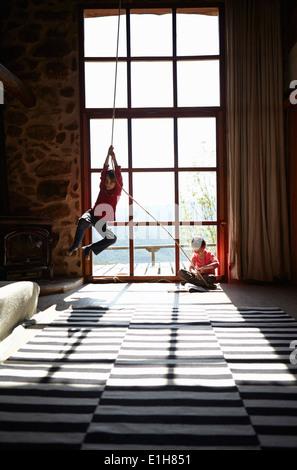 Due fratelli germani in salotto, fratello su swing corda e sorella di lettura Foto Stock