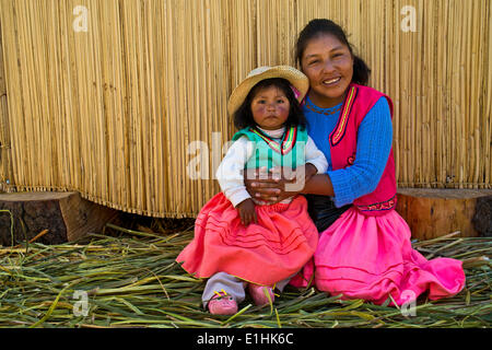 Donna gentile e una ragazza dell'uro indiani indossando vestiti tradizionali seduti davanti ad una capanna di reed, isole galleggianti fatte di