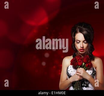 La tenerezza. Donna sognante con bouquet di fiori su sfondo viola Foto Stock