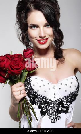 La fragranza. Bella giovane donna Holding bouquet di rose rosse. Il giorno di San Valentino Foto Stock