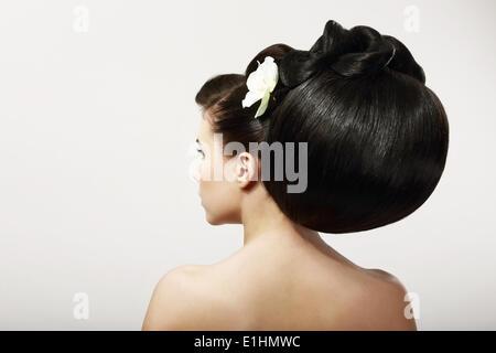 Cura dei capelli -. Retro del modello di moda creative con l'acconciatura. Sana liscia capelli neri con fiore. Spa Foto Stock