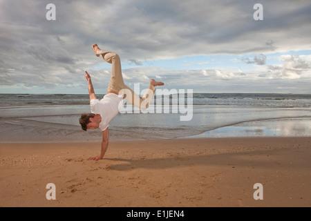 Giovane uomo facendo handstand sulla spiaggia Foto Stock