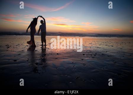 Coppia danzante sulla spiaggia al tramonto, Cape Town, Sud Africa Foto Stock