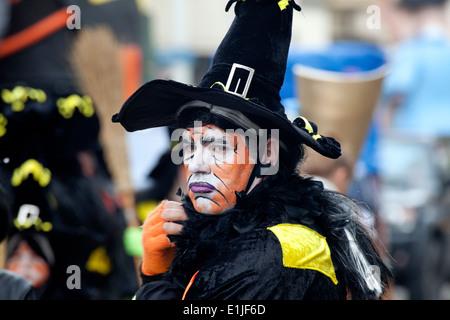 L'uomo sfilano in tradizionale costume strega e di colore arancione faccia vernice, Carnevale di Ostenda, Belgio Foto Stock
