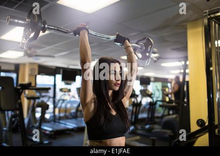 Metà donna adulta utilizzando barbell in palestra Foto Stock