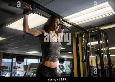 Metà donna adulta facendo esercizio pettorali in palestra Foto Stock
