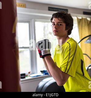 Ragazzo adolescente che indossa guantoni da pugilato Foto Stock