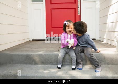 Fratello kissing toddler sorella sulla guancia Foto Stock