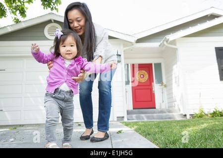 Metà donna adulta femmina e toddler compiendo passi Foto Stock