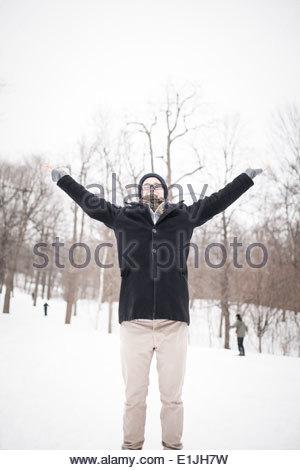 Giovane uomo in piedi nel parco con bracci sollevati Foto Stock
