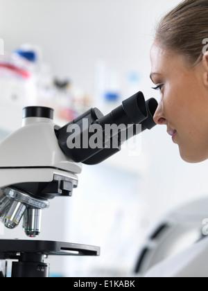 Donna scienziato utilizzando un microscopio. Foto Stock