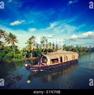 Vintage retrò hipster stile immagine di viaggio del Kerala Viaggi Turismo sullo sfondo - houseboat in Kerala backwaters. Il Kerala, India Foto Stock