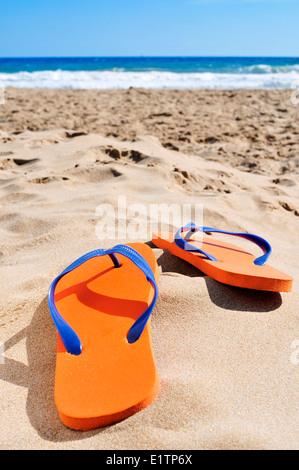 Una coppia di orange flip-flop sulla sabbia di una spiaggia Foto Stock