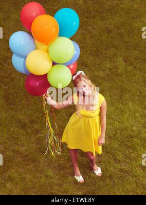 Giovane donna sorridente in piedi sul prato con un mazzetto di coloratissimi palloni di elio nella sua mano. Retrò immagine stilizzata.