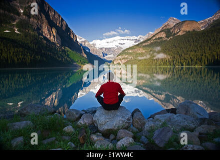 Metà maschio età meditando sulla roccia presso il Lago Louise, Alberta, Canada.