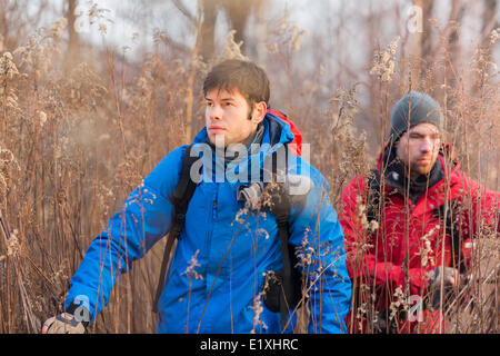 Giovane maschio gli escursionisti a piedi attraverso il campo Foto Stock