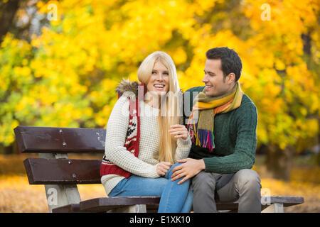 Felice coppia giovane seduto su una panchina nel parco durante l'autunno