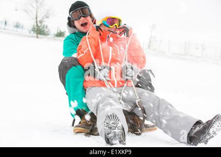 Emozionato coppia giovane slittino nella neve Foto Stock