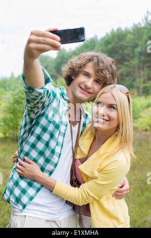 Felice coppia giovane tenendo ritratto di auto attraverso il telefono cellulare nel campo Foto Stock