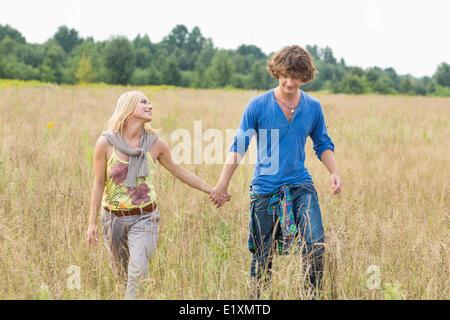 Coppia giovane tenendo le mani mentre si cammina attraverso il campo Foto Stock