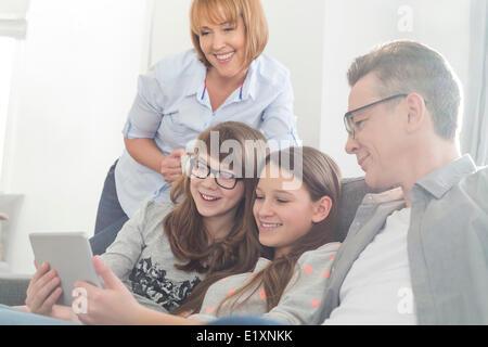 La famiglia felice utilizzando tablet PC sul divano di casa Foto Stock