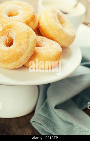 Pausa caffè fresco con ciambelle zuccherine su sfondo bianco Foto Stock