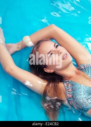 Ritratto di una giovane e bella donna con capelli biondi che indossa un costume da bagno giacente in acqua blu Foto Stock