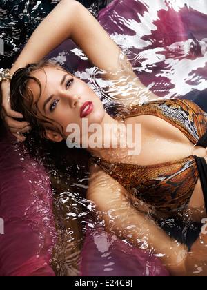 Bellezza ritratto di una giovane donna in un costume da bagno giacente in acqua Foto Stock
