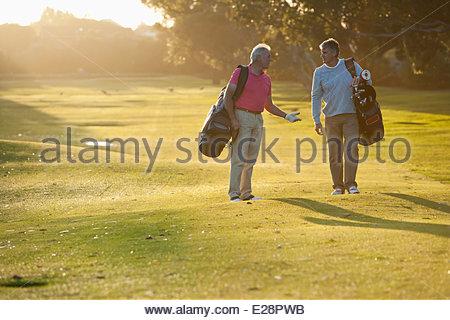 Gli uomini che trasportano le sacche da golf sul campo da golf Foto Stock