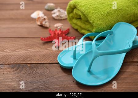 Blue Flip-flop con red starfish e asciugamani su sfondo di legno Foto Stock